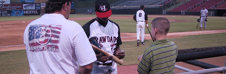 Players sign autographs on the field after the Rickwood Classic